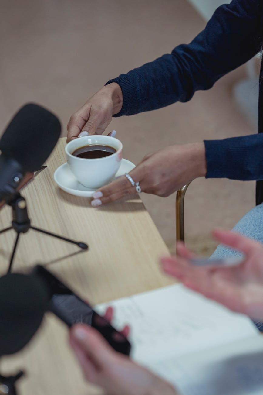 crop diverse women enjoying coffee at desk with microphones